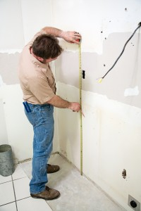 Ellijay, GA Construction worker measuring the wall during a kitchen remodeling job.  Authentic and accurate content depiction.